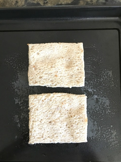 Two slices of bread on a baking pan with the crusts removed