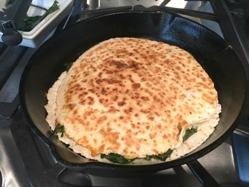 a quesadilla cooking in a cast iron skillet