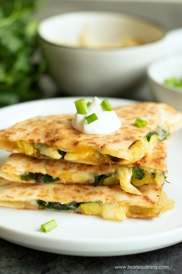 A stack of cut delicata squash quesadillas on a white plate. The quesadillas are garnished with sour cream and scallions.