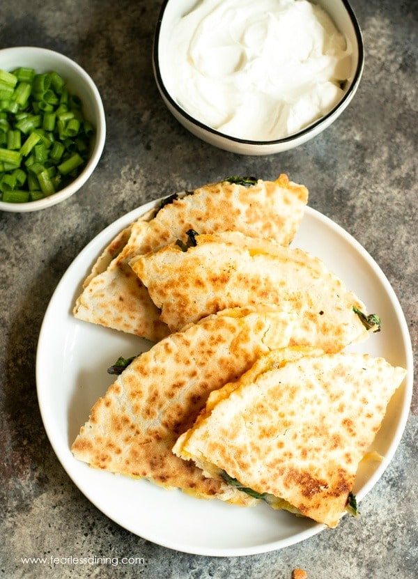 sliced pieces of quesadilla on a plate. A bowl of sour cream and a bowl of scallions are next to the plate