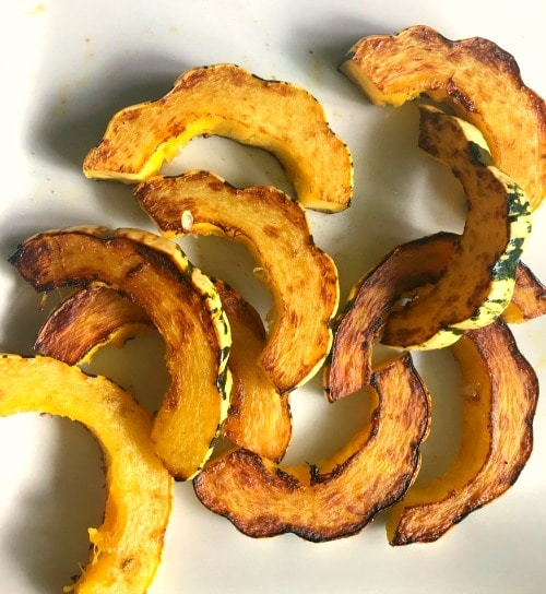 Cooked slices of delicata squash on a plate