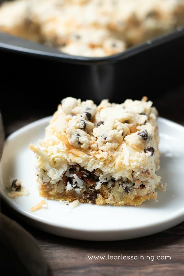 a gluten free cookie dough 7 layer bar on a plate. The pan of bars is behind the plate