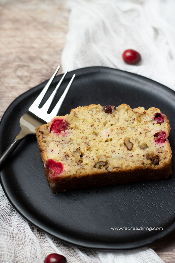 a slice of banana cranberry bread on a plate