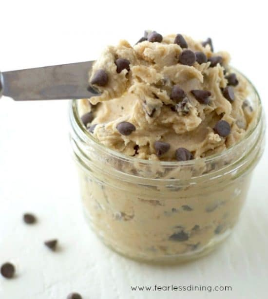 a knife dipping into a jar of homemade gluten free cookie dough