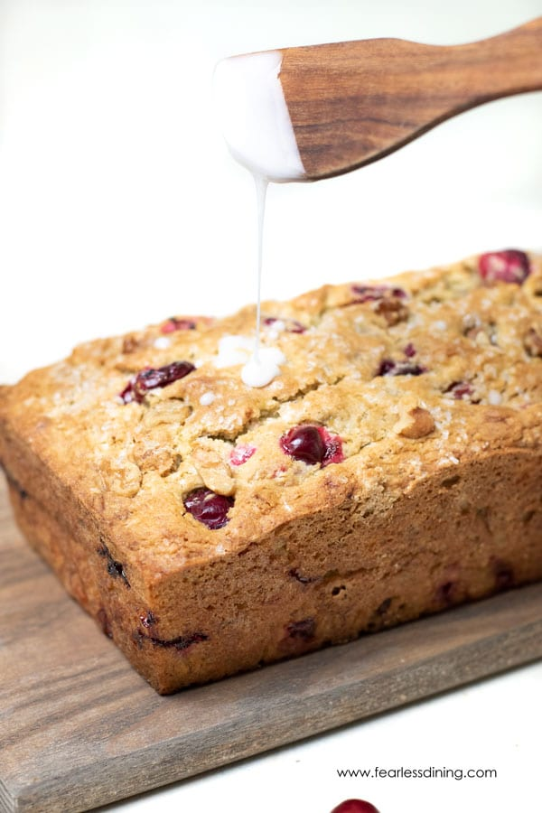 drizzling icing on a cranberry banana bread loaf.