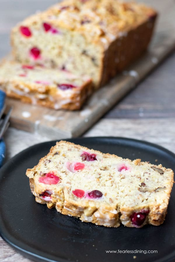 a slice of gluten free cranberry banana bread on a plate. The whole loaf is behind the plate