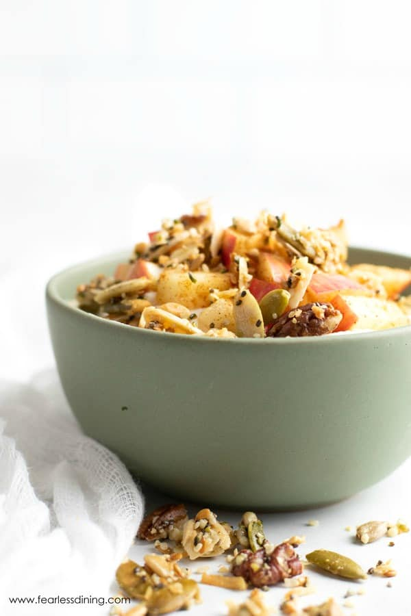 granola topped cinnamon apples over yogurt in a green bowl