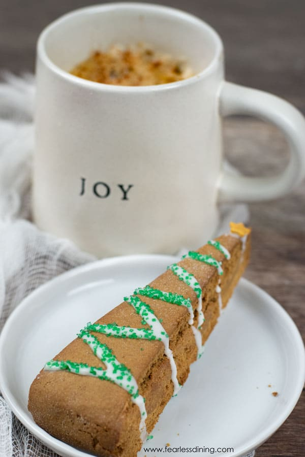 a gingerbread biscotti on a plate next to a mug of coffee