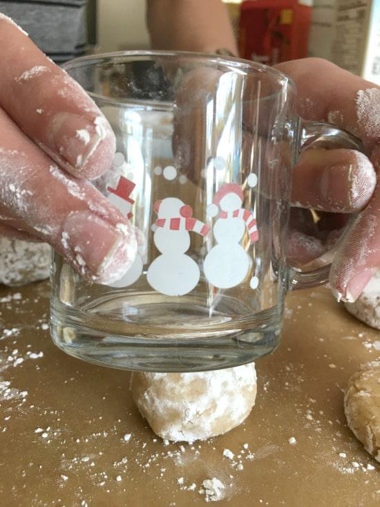 using a mug to smoosh the cookie dough balls flatter.