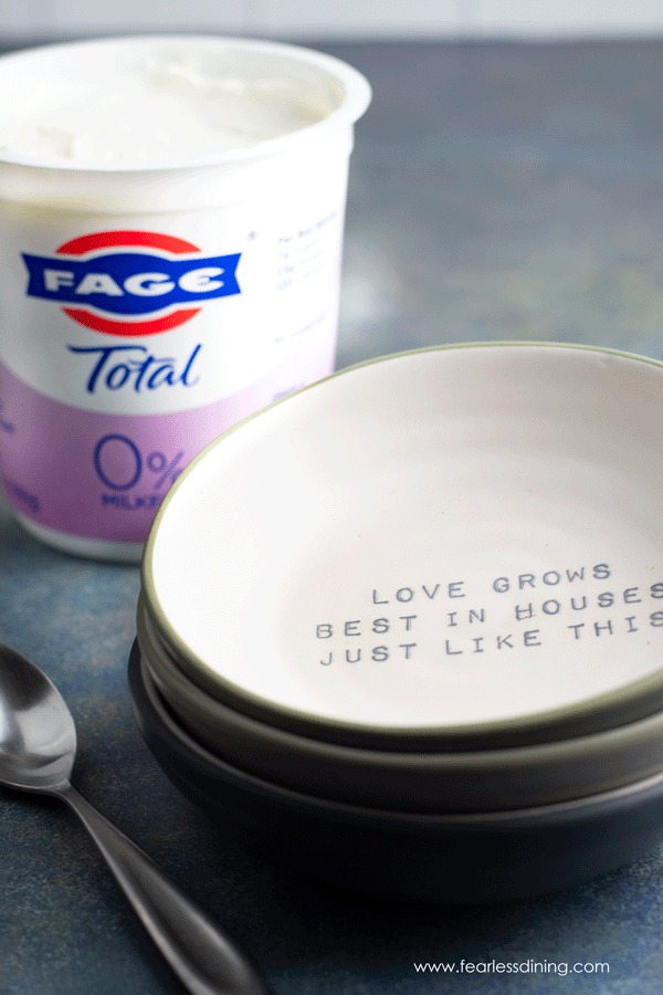 a container of FAGE Greek yogurt next to empty bowls
