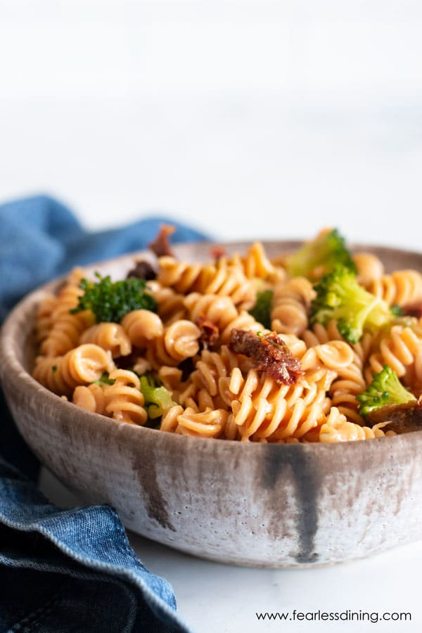 a close up of gluten free pasta salad with sun-dried tomatoes and broccoli