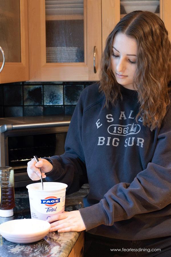 K adding yogurt to a bowl