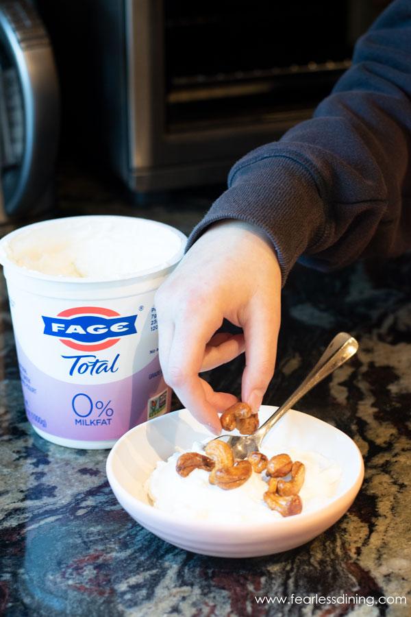 Adding cashews to a bowl of yogurt