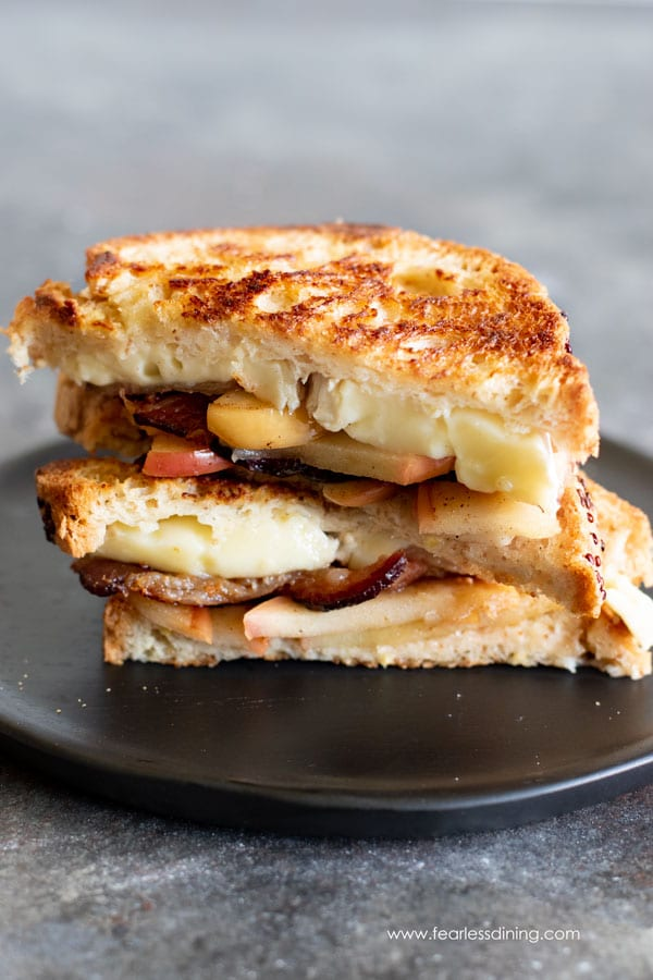 a grilled brie cheese sandwich cut in half and stacked on a plate.