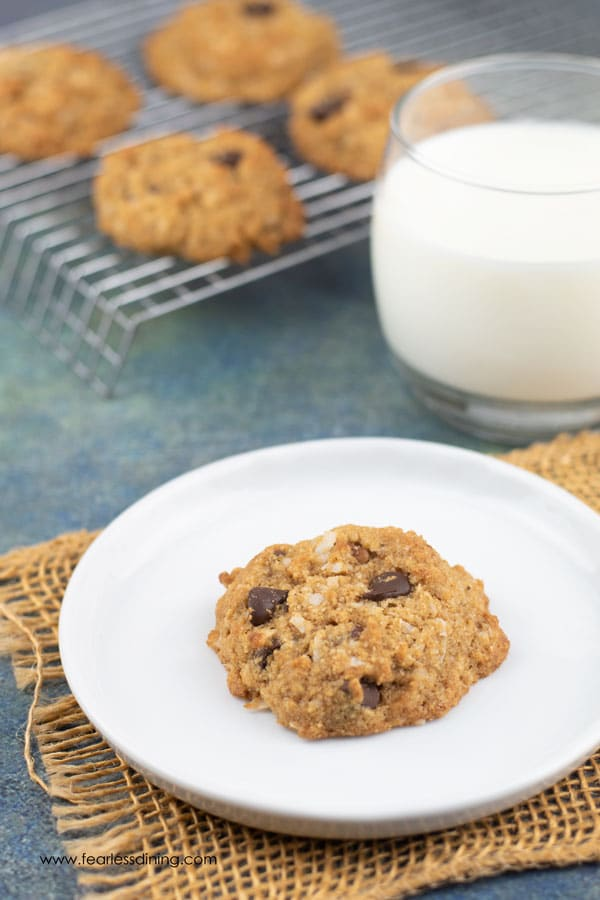 a paleo almond flour chocolate chip cookie on a plate next to a glass of milk.