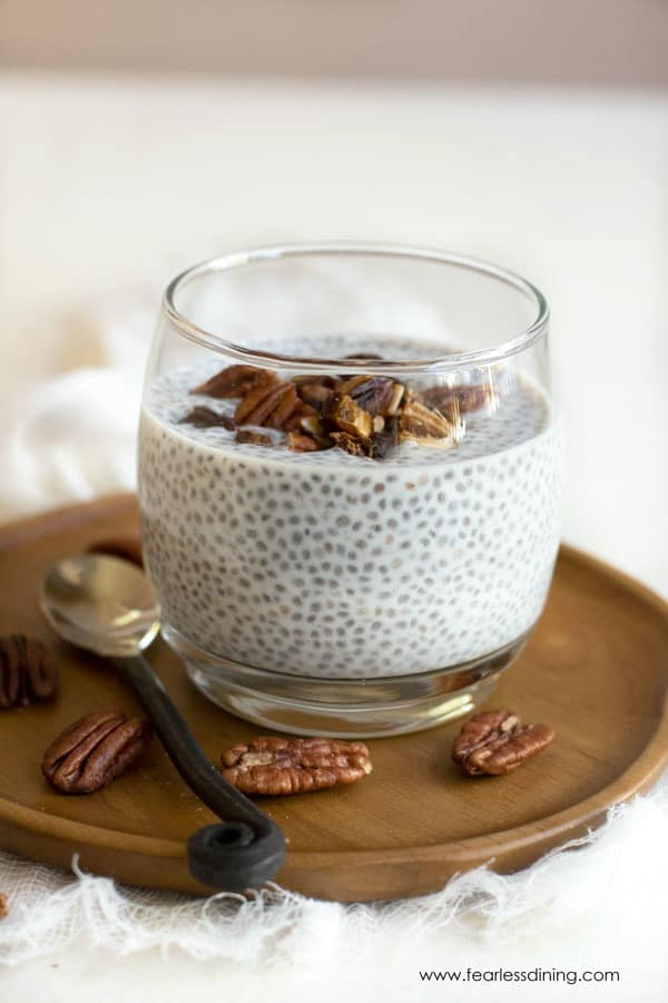a glass filled with vanilla chia pudding. This is topped with chopped dates and pecans