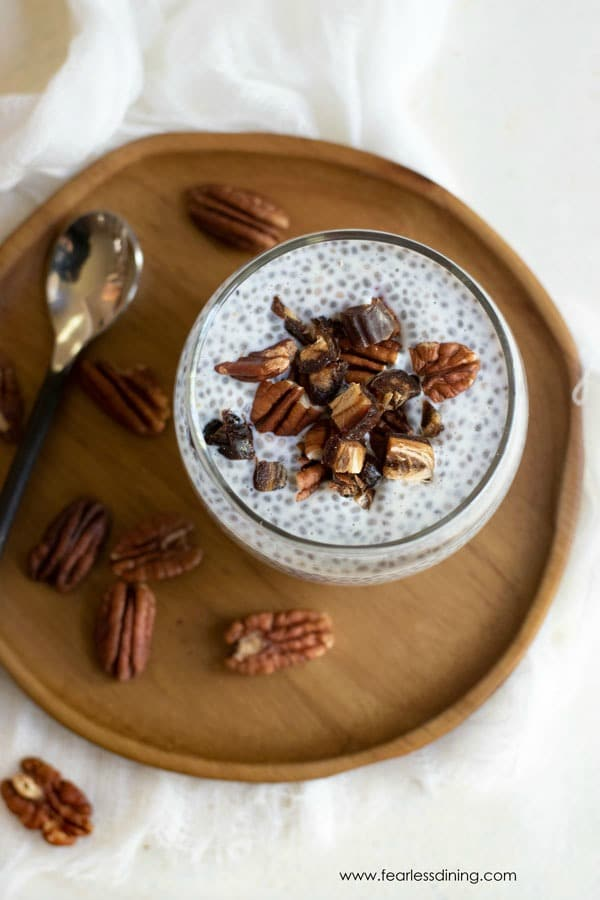 top view of vanilla chia seed pudding in a glass with pecans around the plate