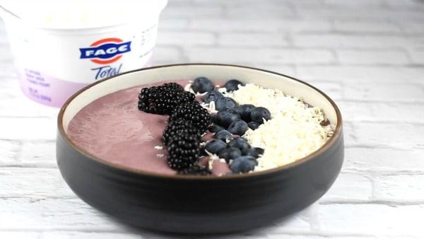 adding fresh blackberries to the smoothie bowl