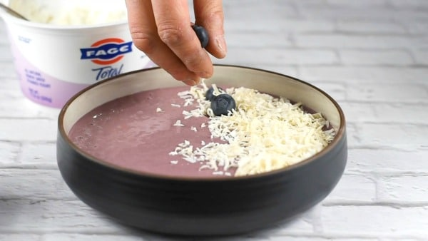 adding blueberries to the smoothie bowl