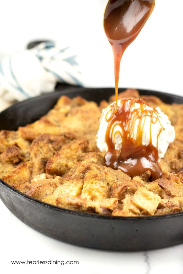 a spoon drizzling caramel over the skillet of gluten free banana bread pudding