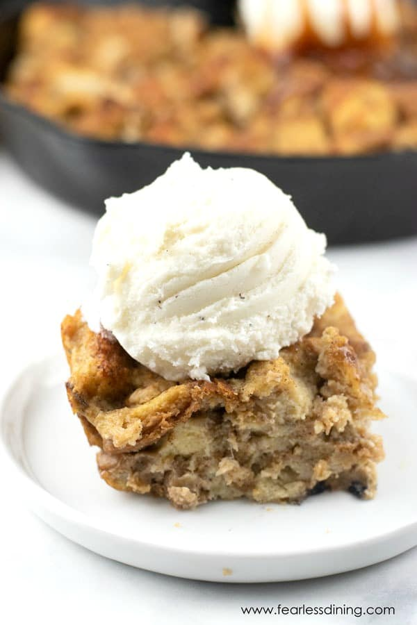 a slice of gluten free banana bread pudding on a plate with vanilla ice cream on top