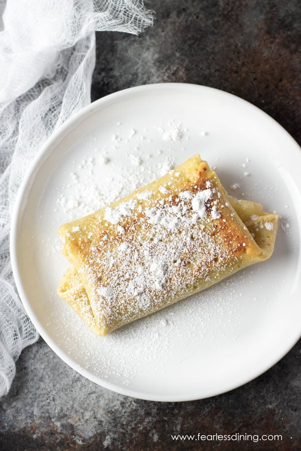 a folded cheese blintz on a plate with powdered sugar