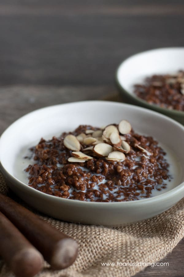 two bowls of gluten free chocolate steel cut oats with milk and almond slices