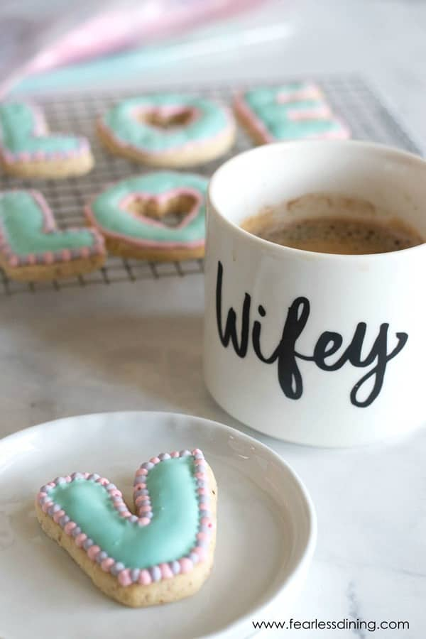 A V shaped decorated cookie on a plate next to a mug of coffee