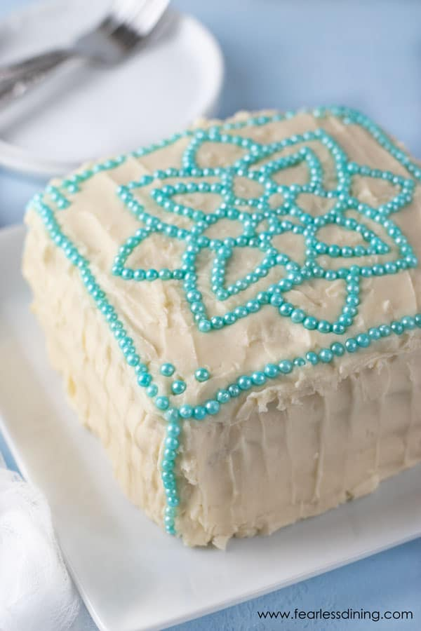 a gluten free vanilla layer cake. The cake has a mandala design on top with turquoise colored round ball sprinkles
