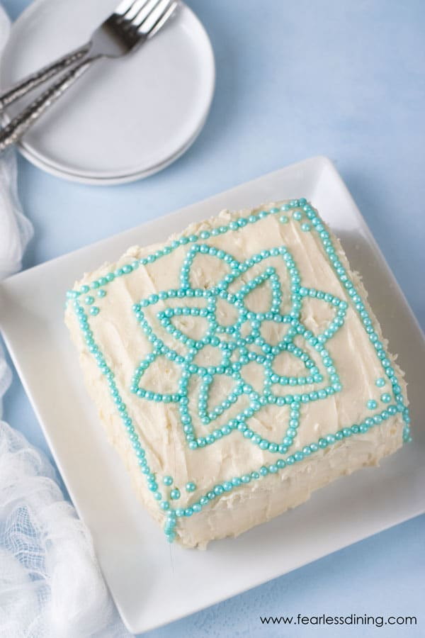 top of a gluten free vanilla cake. There is a mandala design on top made with turquoise ball shaped sprinkles