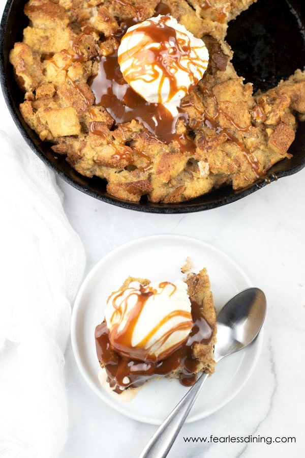 top view of a plate of gluten free banana bread pudding with caramel and ice cream next to the skillet of bread pudding