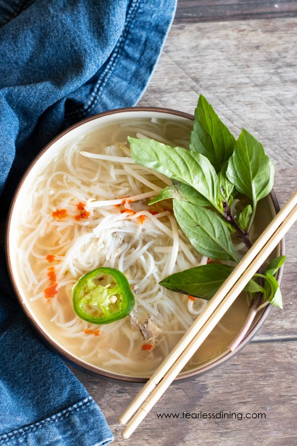 a bowl of chicken pho with chopsticks on the side of the bowl