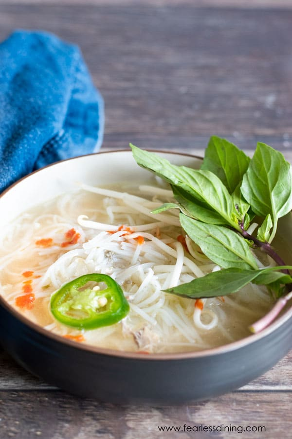 A bowl of chicken pho garnished with fresh basil and jalapeño.