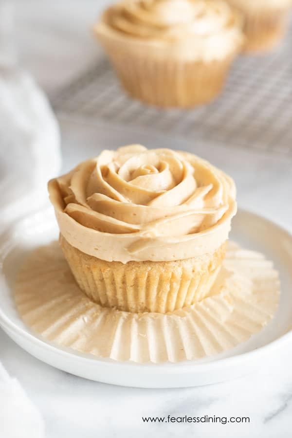 a gluten free caramel cupcake on a plate with the paper liner peeled