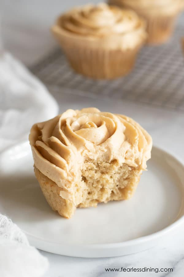 a gluten free caramel cupcake on a plate with a bite taken out