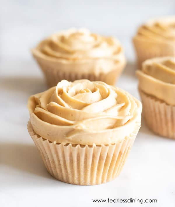 a close up of a caramel cupcake with frosting like a rose