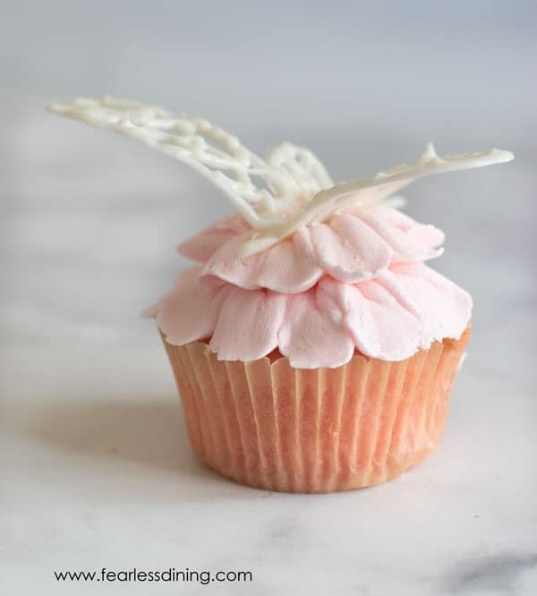 Another shot of the white chocolate dragonfly on a pink floral cupcake
