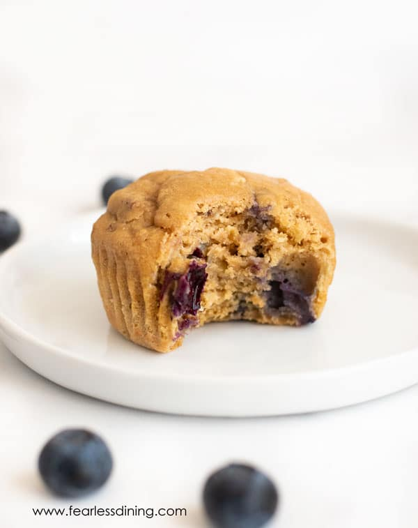 a blueberry protein muffin with a bite taken out on a plate