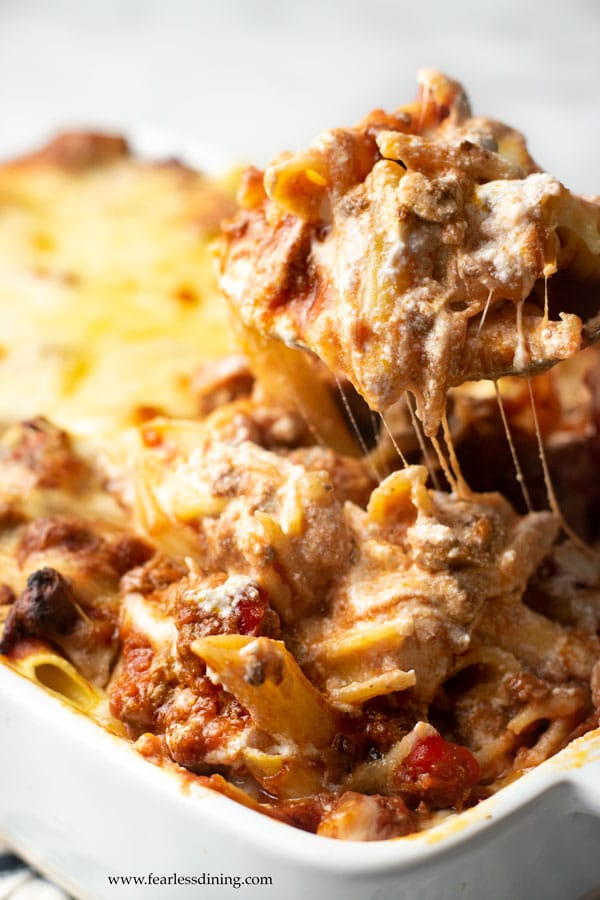 a spoon lifting ziti casserole with cheese stretching