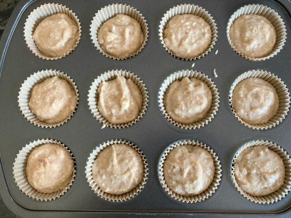churro muffin batter in a muffin tin