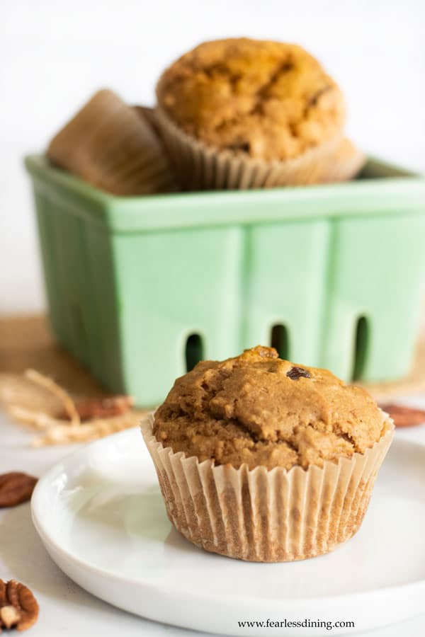a gluten free banana muffin on a plate with a basket of muffins in the background.