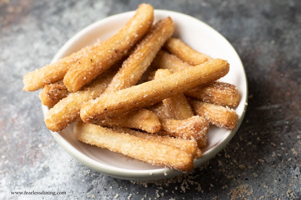 a bowl of gluten free churros ready to eat