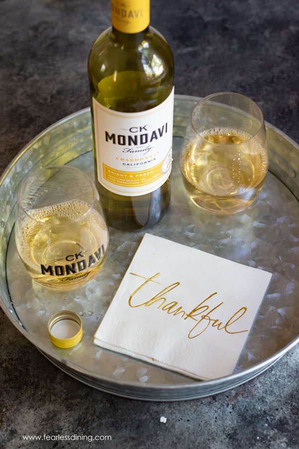 a bottle of CK Mondavi Chardonnay with two glasses of wine on a tray
