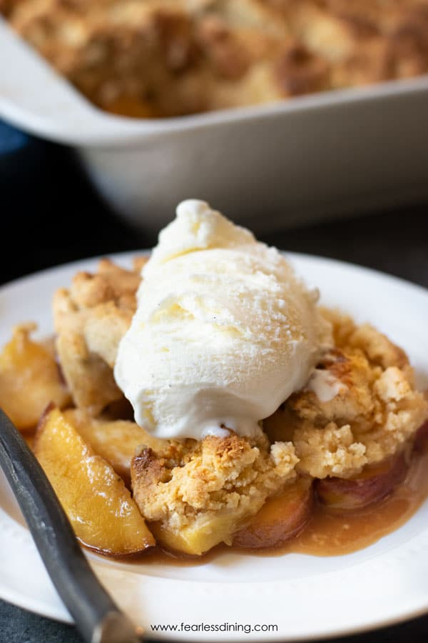 a close up of the paleo peach cobbler with ice cream topping