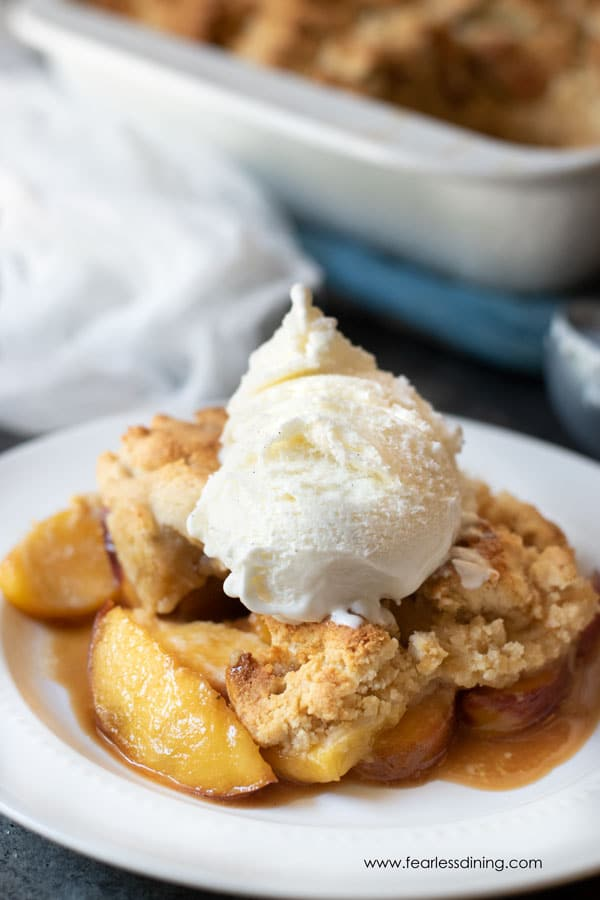 a serving of paleo peach cobbler topped with vanilla ice cream