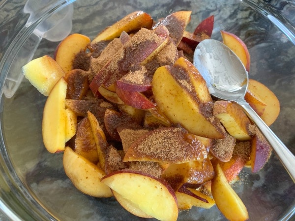 sliced peaches in a a bowl with coconut sugar