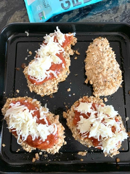 adding mozzarella cheese to the chicken cutlets