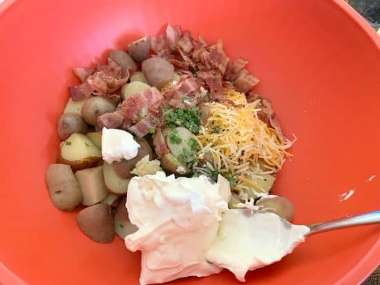 bacon, potatoes, chives, cheese and sour cream in a bowl
