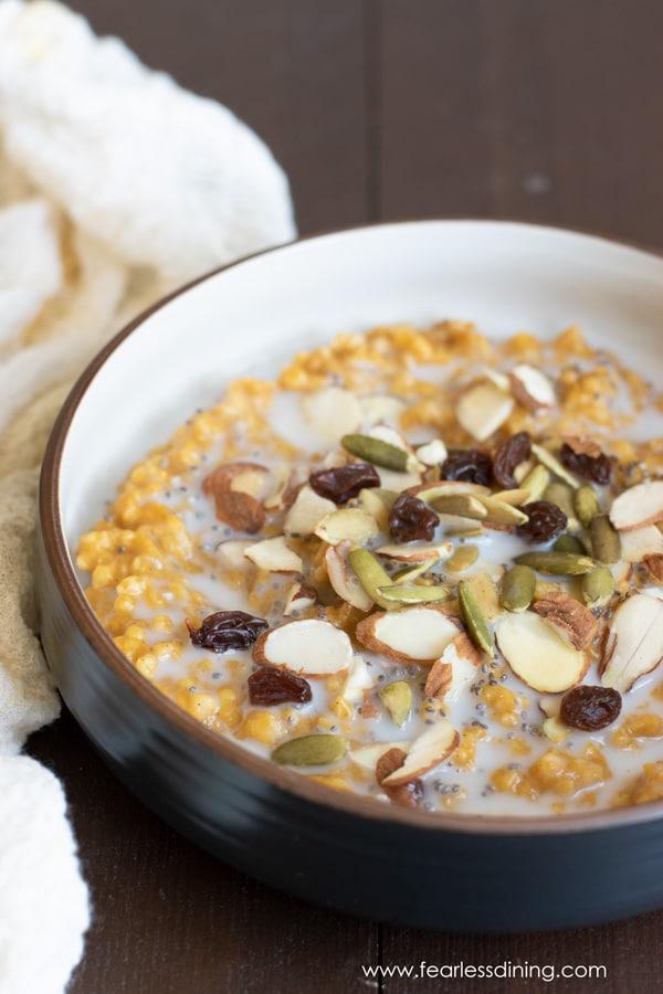 a bowl of slow cooker pumpkin steel cut oats topped with raisins, almonds, and pumpkin seeds