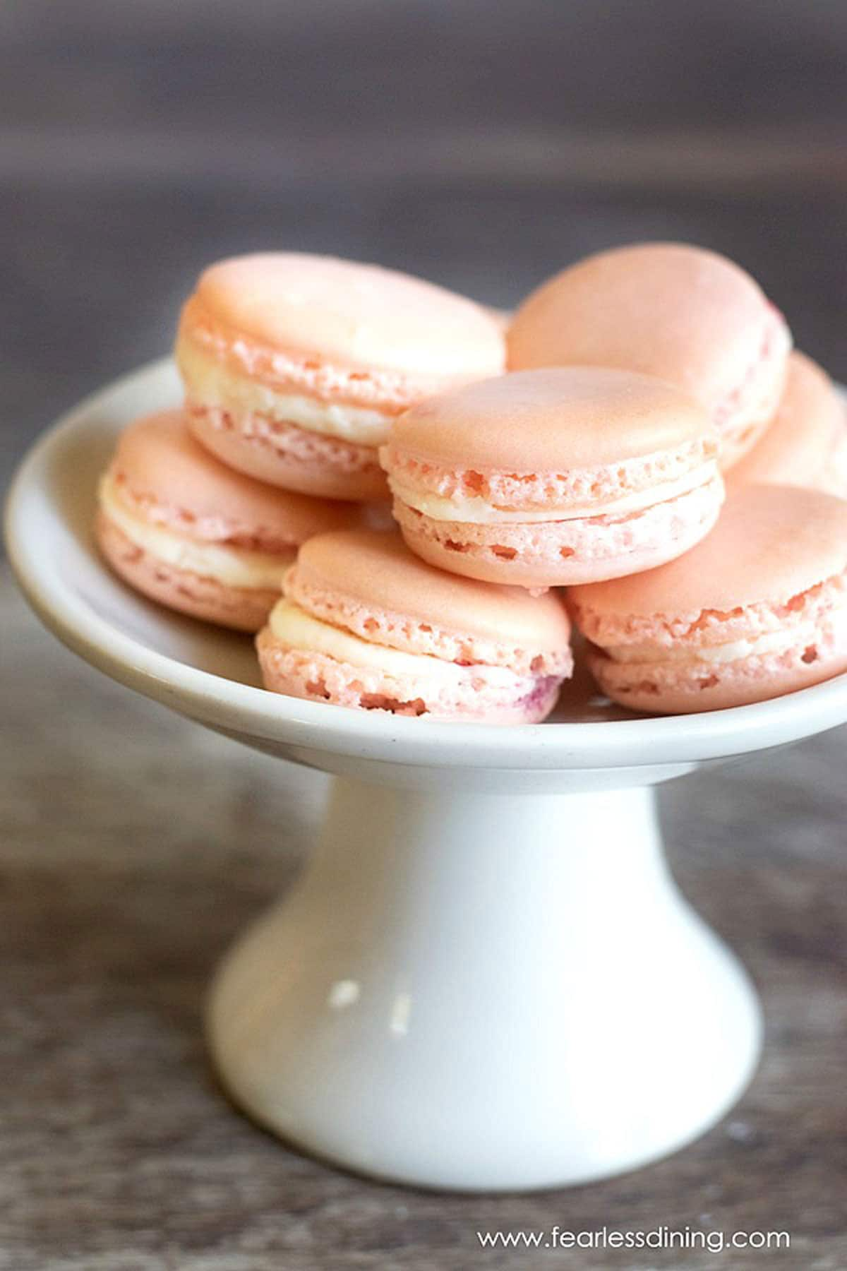 a white platter filled with raspberry macarons